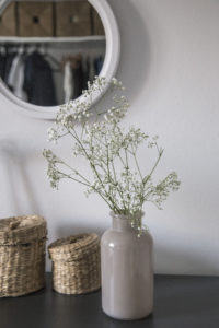 vase of flowers and a mirror