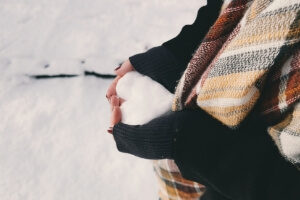 woman holding heart shaped snow in her hand