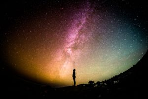 silhouette of person looking at milky way in sky
